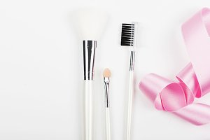 Makeup brushes with pink ribbon. Background. Copy space.