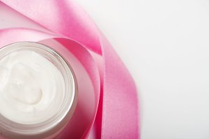 Bottle of cream for face next to pink ribbon on white background. Copy space.