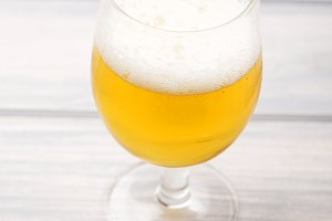 Close-up of a glass of beer on wooden table. Vertical shoot.