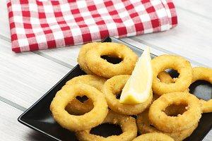 Close-up of a plate of squid a la romana, a lemon on a black plate. Squids.Horizontall shoot.
