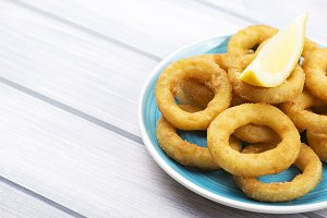 Plate of squid a la romana and a lemon on white wooden table. Squids. Horizontal shoot....