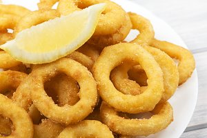 Close-up of platter of squid to la romana and a lemon on white wooden table. Squids.