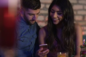 Couple using mobile phone in bar