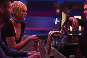 Bartender interacting with a couple at counter