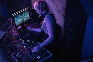 Female dj mixing music in bar