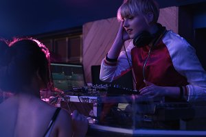 Female dj playing music while interacting with woman