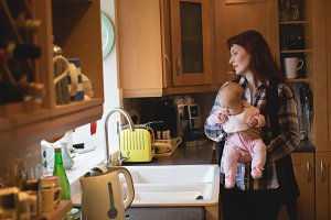 Mother holding her little baby in kitchen