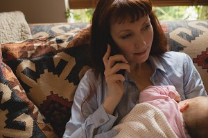 Mother talking on mobile phone while breast feeding her baby on sofa