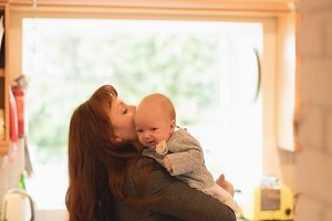 Affectionate mother holding her baby in kitchen