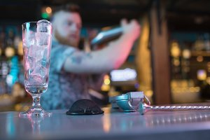 Bartender preparing a drink with bar accessories at counter