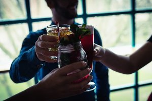 Friends toasting glasses of drinks in bar