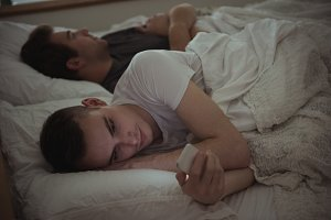Man checking his mobile phone while lying on the bed with his gay partner