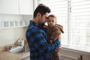 Father holding his baby boy while standing in kitchen