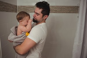 Father holding his baby in bathroom
