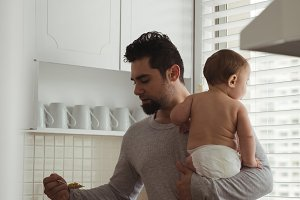 Father having breakfast while holding his baby