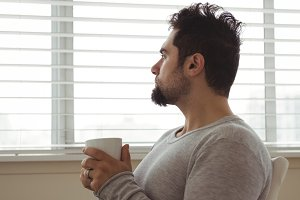 Thoughtful man holding a coffee cup