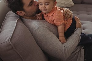 Father kissing his baby on sofa in living room