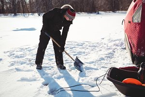 Ice fisherman digging with shovel