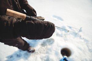 Ice fisherman holding fishing rod