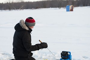 Ice fisherman fishing in snowy landscape
