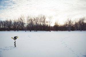 Ice fishing drill in snowy landscape