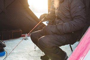 Ice fisherman fishing while sitting