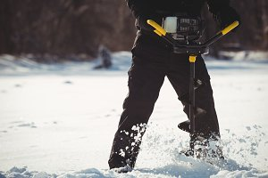 Ice fisherman drilling in the snow