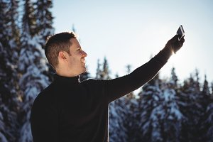 Smiling man taking selfie on mobile phone