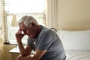 Worried senior man sitting on bed in the bedroom