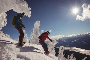 Two skiers skiing in snowy alps