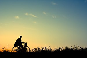 Silhouette of man and old bicycle
