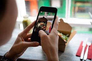 Woman clicking a photo of salad from mobile phone