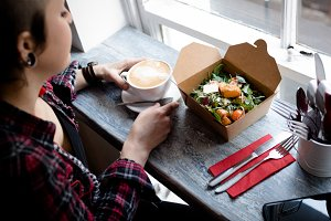 Woman having coffee and salad in café