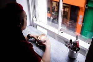 Woman having coffee in café