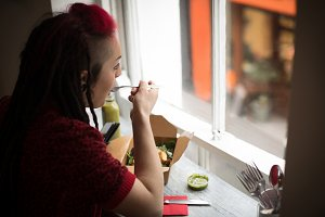 Woman looking through window while having a salad