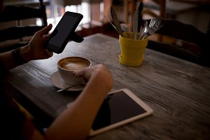 Woman using mobile phone in café