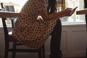 Woman using mobile phone near window