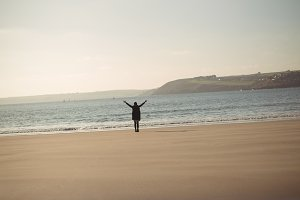 Woman standing with her arms outstretched on beach during day
