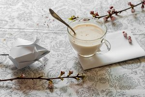 Hot coffee with milk and cinnamon. Spring branches