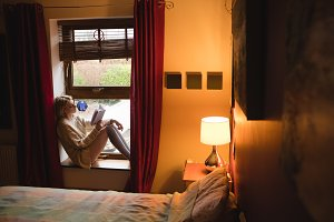 Woman sitting on window and reading a book