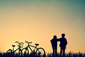 Silhouette of children with bicycle