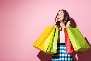 Smiling young woman buyer holding shopping bags and looking away