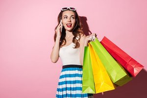 Portrait of a young smiling woman holding colorful shopping bags