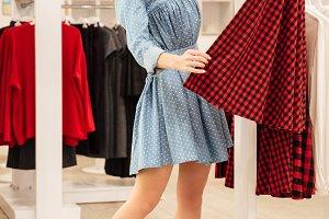 Smiling woman shopper in blue dress choosing clothes