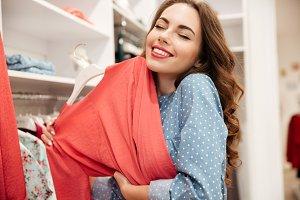 Smiling young woman shopper choosing clothes.