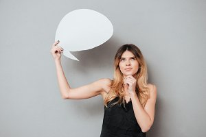 Portait of a lovely pensive girl holding speech bubble