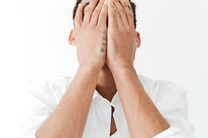 African man isolated over white background covering face