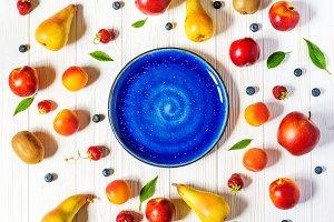 Summer fruits around blue plate