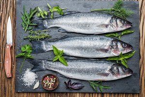 Three fish - seabass on a graphite board with spices and herbs.