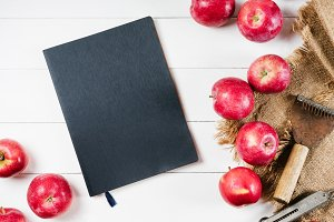Notebook and apple on linen textiles